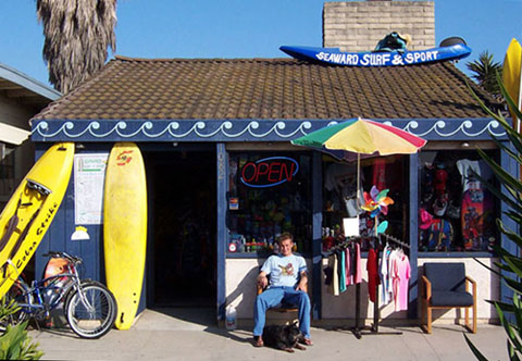 Storefront of a Surf Shop at Ventura, CA Beach with a Kayak sign and surfboards, T-shirts, Sweatshirts, and beach cruiser bicycles out front.